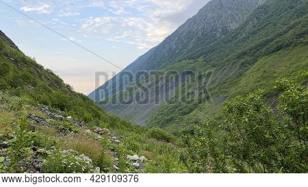 Rocks, Green Hills, Blue Sky And White Clouds. Mountain Landscape Of North Ossetia. Climbing Kazbek