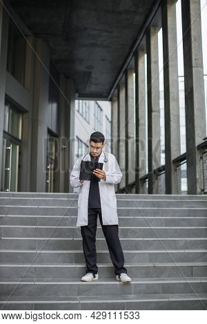 Full Length Of Young Handsome Skilled Male Arab Heathcare Worker, Making Notes On Folder Clipboard,