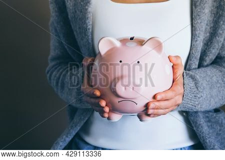 Female Hands Holding Sad Unhappy Piggy Bank. Close Up Woman Holds Thrift Box. Financial Problems And