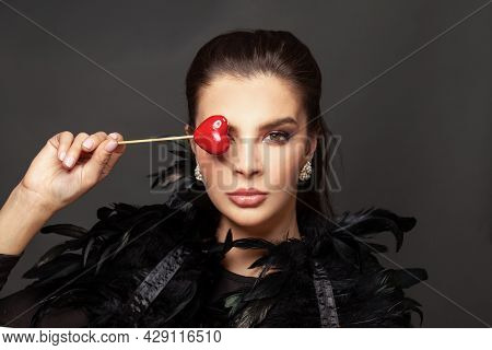 Stylish Young Woman Brunette And Red Heart On Black Background. Beautiful Fashion Model With Makeup.