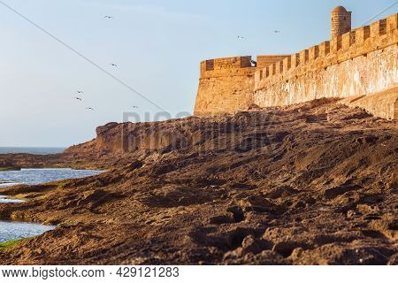 View Of The Historical Walls Of The Essaouira Fortress And Volcanic Shore Of The Atlantic Ocean In M