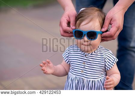 Hands Of Father Putting Sunglasses On Little Daughter During Walk Outdoors . Close Up Photo: Dad Put