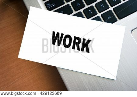 White Sticky Note Reminder On Laptop Keyboard With Work Word. Paper Note On Computer.