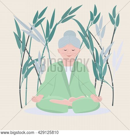 An Old Woman Granny Does Yoga In The Lotus Position On A Bamboo Background. The Concept Of A Healthy