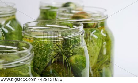 Closeup Glass Jars Filled With Fresh Cucumbers,dill,garlic And Black Pepper And Poured With Brine Wh