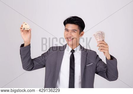 Young Asian Business Man Holding Home And Money Thai For Planning Saving Future, Insurance Agent And