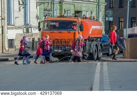 St. Peteburg, Russia - April 18, 2021: Schoolchildren Cross The Street In Front Of A City Utility Tr