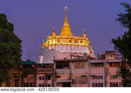 Stupa Of The Golden Mountain Temple (wat Saket) In The Evening Illumination In The Cityscape. Bangko
