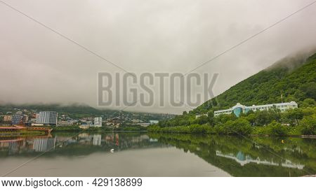 There Is Fog Over The City Lake. The Peaks Of The Mountains Are Hidden In Dense Clouds. Houses And T