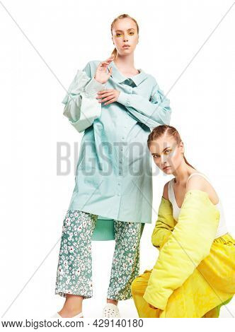 Haute couture clothing. Fashion models girls pose in stylish clothes from the summer collection. Full length studio portrait on a white background.