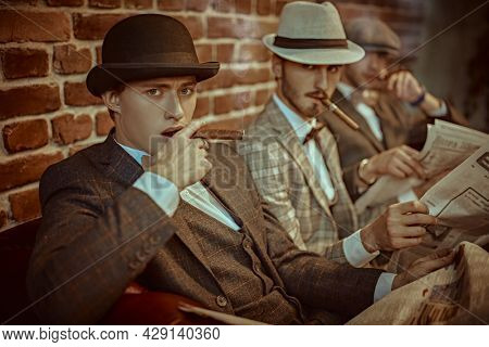 Three handsome men in elegant suits sit on a leather sofa, smoke cigars and read newspapers. Newspaper editorial office. Retro style. Men's fashion.