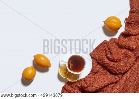 Autumn Background With Tea And Knitted Sweater On White Background. Hot Herbal Lemon Tea With Orange