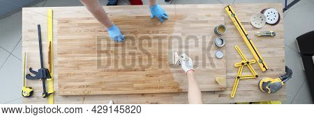 Two Craftsmen Are Covering Wooden Table With Protective Varnish
