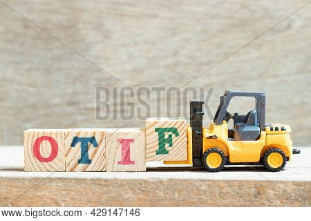 Toy Forklift Hold Letter Block F To Complete Word Otif (abbreviation Of On Time In Full) On Wood Bac