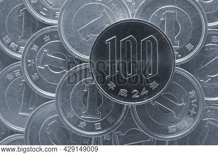 100 Yen Lies On A Pile Of Japanese 1 Yen Coins. Gray Tinted Background Or Wallpaper On A Financial T