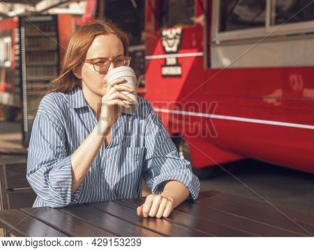 Young Woman Sitting Alone With Collapsible Eco Coffee Cup Near Street Food Truck. Modern City Lifest