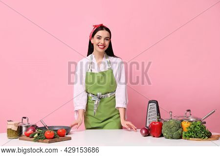 Young Housewife At White Table With Utensils And Products On Pink Background