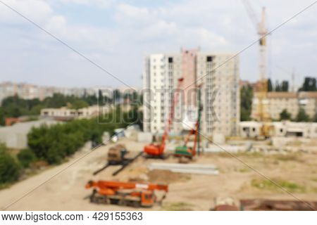 Blurred View Of Construction Site With Heavy Machinery Near Unfinished Building