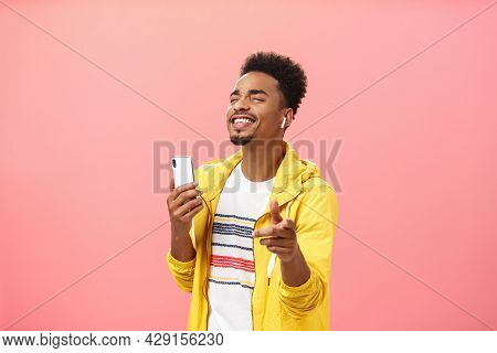 Joyful Handsome African American With Afro Hairstyle And Beard Closing Eyes And Smiling With Delight