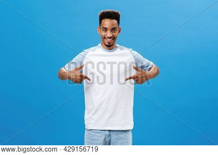 Pleased And Delighted Good-looking Man Showing Cool T-shirt Pointing At Himself With Proud Satisfied