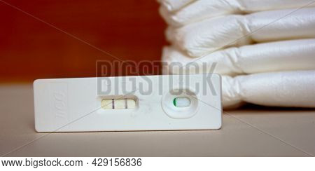 Positive Pregnancy Test And Diapers. Motherhood, Children, Pregnancy, The Concept Of Birth Control.