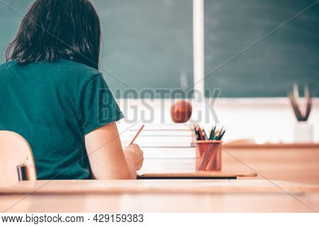 High school or university student holding pencil writing on paper answer sheet. Final exam concept.