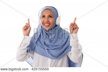 Music And Technology Concept-young Happy Asian Muslim Woman Enjoing Using Headphone To Listen The Mu