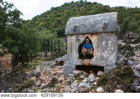 Hiking Lycian way. Tourist posing for photo inside Lycian rock tomb, stretch between Myra - Alakilise Ruins, Trekking in Turkey, outdoor activity, Ancient stone sarcophagus of Lycian necropolis