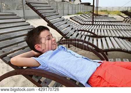 Happy Teenage Boy Lying Down On A Wooden Chaise Lounge. Handsome Child Resting On The Deck Chair Dur