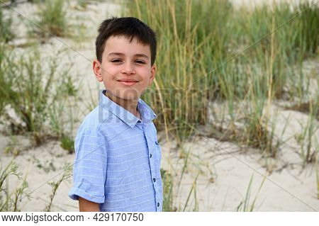 Close-up Of The Face Of A Cute Smiling Teenage Boy Standing Against The Backdrop Of Steppe Thickets