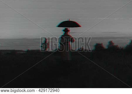 Surreal Silhouette Of A Man In A Suit With An Umbrella, Standing In A Raincoat In A Field. The Conce
