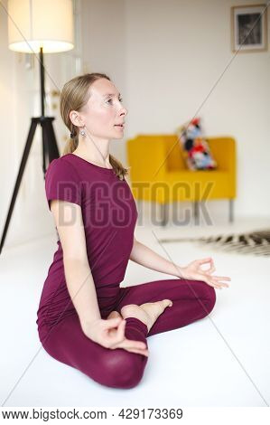 Blond Female In Sportswear Sitting With Crossed Legs And Mudra Hands On Mat And Doing Yoga While Pra