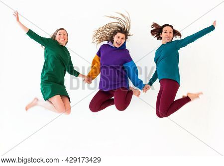 Image Of Three Happy Playful Barefoot Women Of Different Age Holding Hands Together, Jumping And Hav