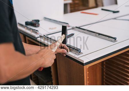 Man Nailing A Wooden Stud With A Hammer To A Surface Of A Furniture In A Workshop