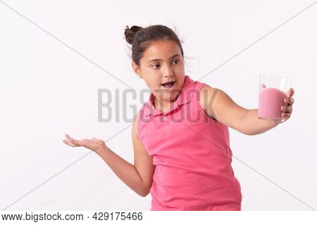 Little Girl Holding A Glass With A Pink Drink With An Astonished Face