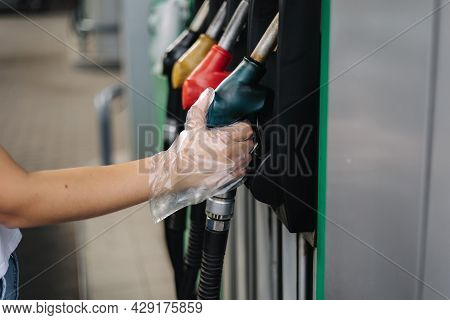 Close-up Of A Womens Hand Using A Fuel Nozzle At A Gas Station. Petrol Station Concept. Filling Stat