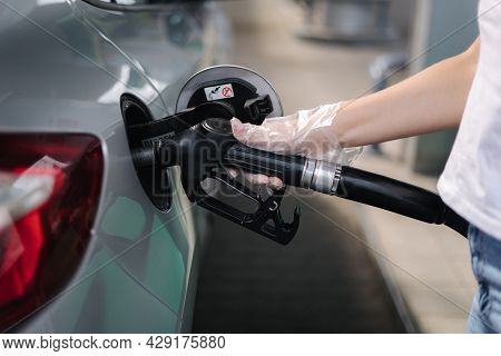 Woman Is Refueling At Gas Station. Female Hand Filling Benzine Gasoline Fuel In Car Using A Fuel Noz