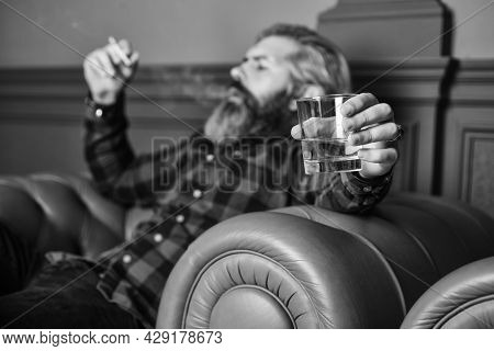 Brutal Bearded Hipster Smoking Cigarette Drinking Alcohol While Relaxing On Leather Armchair. My Swe
