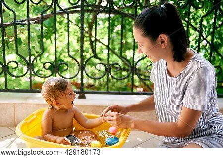 Mom Lathers A Little Laughing Girl In A Basin On The Balcony