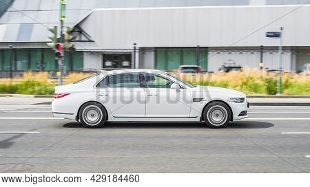 White Genesis G90 Facelift Cruising The Streets. Motion Image Of Premium Shiny Car Running On The Ci