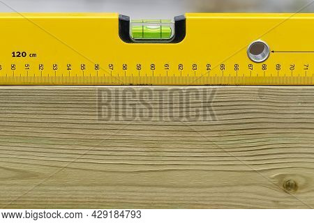 Yellow Spirit Level Levelling Horizontal On Wooden Board. Construction Worker Tool Measurement Tool