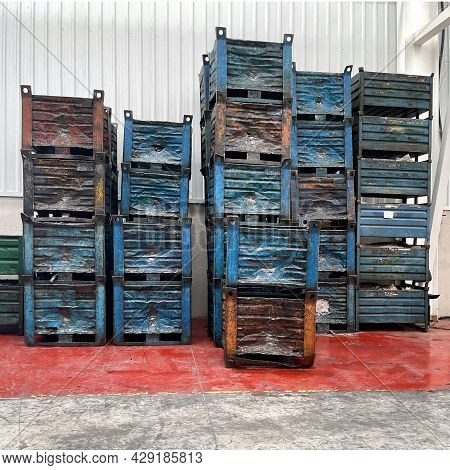 Dented Blue Metal Containers Stacked On A Shed With A Red Floor And White Walls, Square Format