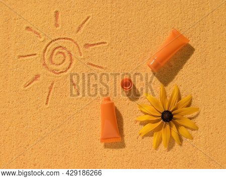 Sunscreen, A Flower And A Painted Sun On Yellow Sand. Sun Protection Cream.
