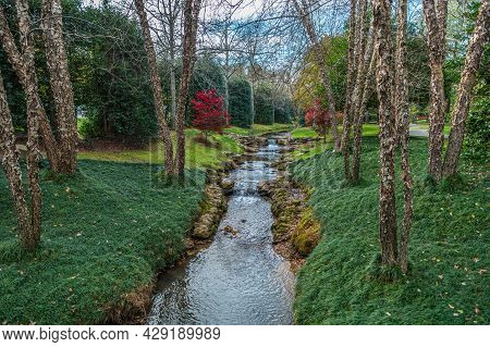 A Well Manicured Park With A Stream With Mini Waterfalls Spilling Over The Rocks Alongside The River
