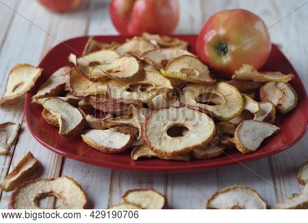 The Benefits Of Dried Fruits And Vegetables. Dried Apple Chips And Red Fresh Apples On A White Woode