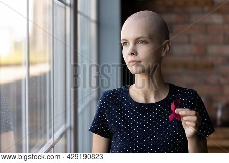 Thoughtful Female Oncology Patient Holding Red Ribbon