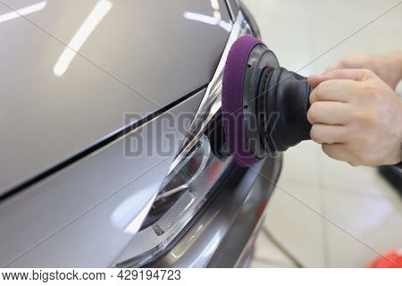 Hands With Orbital Polisher In Car Workshop Polishing Headlight Of Car