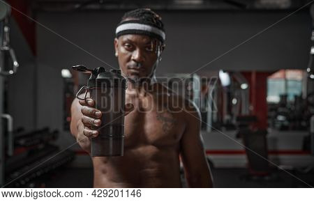 Athletic African American Man With Naked Torso Showing Sports Glass With Water Or Sports Nutrition O