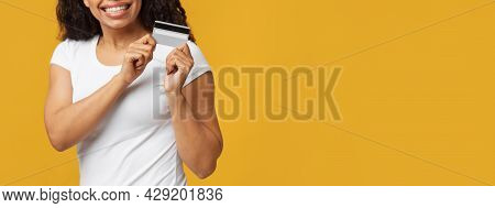 Digital Payment Concept. Unrecognizable Woman Holding And Showing Plastic Debit Credit Card Over Yel