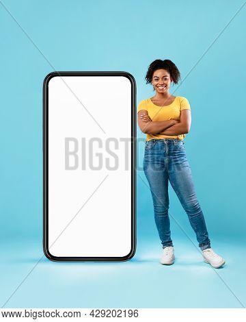 Beautiful Afro Lady Standing Near Huge Smartphone With Empty White Screen On Blue Background, Mockup